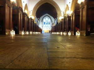 A photo of the central aisle at St Mary's, lined by candles for a New Year's eve wedding