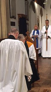 A photo of David kneeling before the Archdeacon as his licence is read aloud.