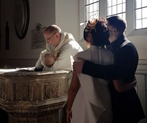 David baptises a baby while his parents look on.